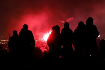 Revellers watch fireworks over Vienna on a hill in Perchtoldsdorf minutes before the New Year, Austria