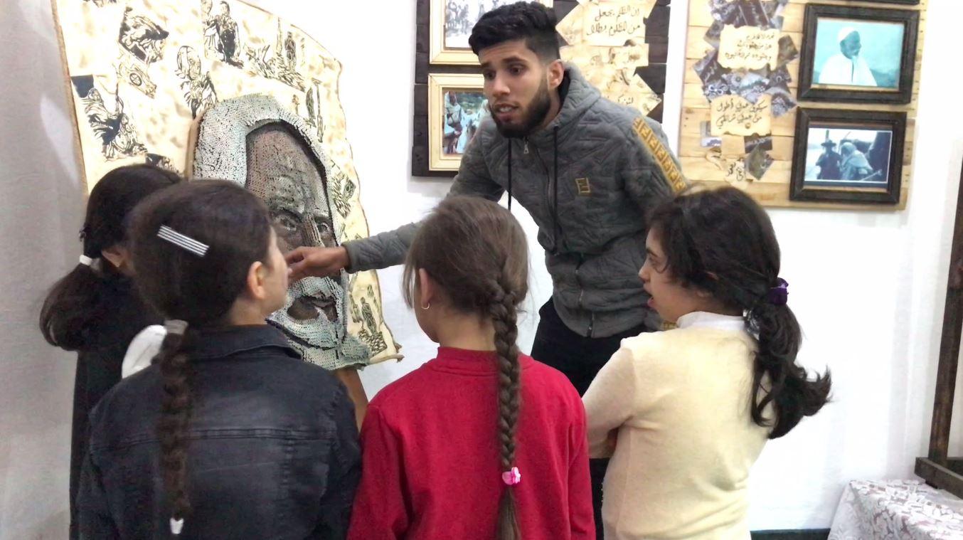 طالب من جامعة عمر المختار يشرح لوحته للتلاميذ في درنة