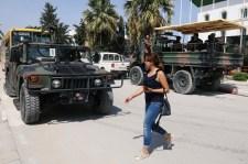 A woman walks past army soldiers outside a sports hall where ballot boxes and election material are collected to be distributed to polling stations in Tunis