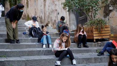 التلاميذ يجلسون على درج في شارع بوسط نابولي
