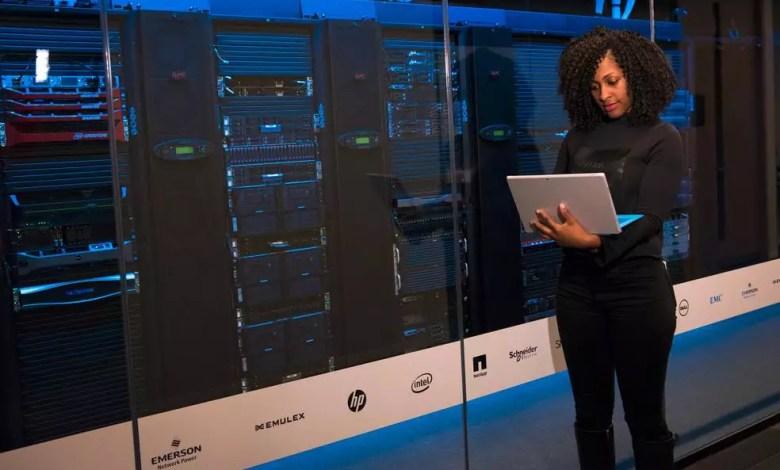 une dame devant des serveurs avec son laptop