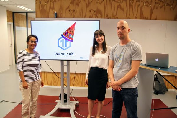 """Eva Westerhoff, Irene Frijns and Job van Achterberg are standing in front of a presentation slide, showing the idea11y logo wearing a party hat, and the text """"one year old!"""""""