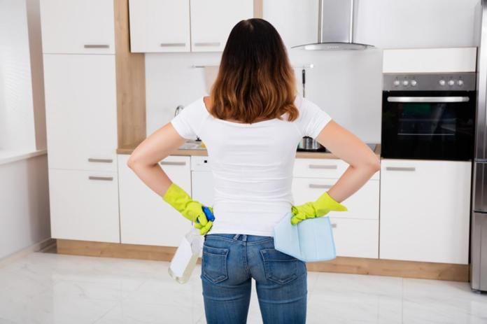 Woman Standing In Kitchen Using Cleansing Product   Autor: Dreamstime