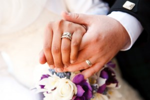 White hands with wedding rings.