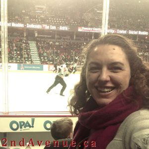 A grinning Laura in the stands at a Hitmen hockey game