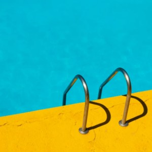 A bright yellow pool deck with a chrome ladder that leads to turquoise water - you SHOULD dive in