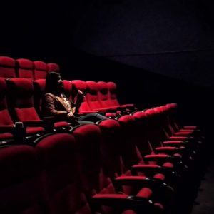 A woman sits alone in a dark theatre with red velvet seats