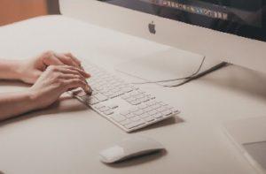 Hands Typing on a Mac Desktop