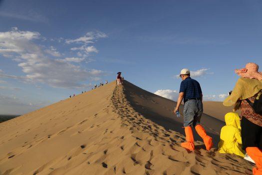 Walking along the ridge of a sand dune in mingsha dunhuang