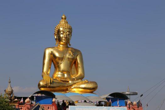 A golden Buddha statue sits near the Golden Triangle waterfront park