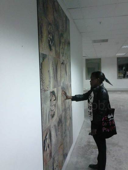 Nyasha Sengayi looks at a large mural of pictures of potholes