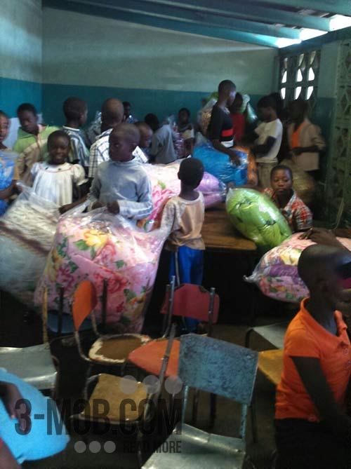 Kids receive blankets from Arsenal Zimbabwe Fan Club members at Felly Children's Home
