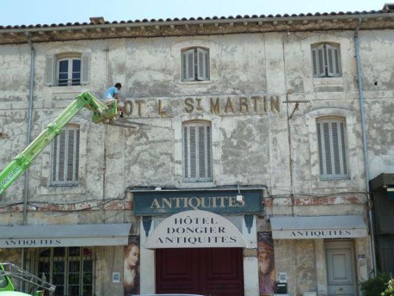 Ein Arbeiter schlägt die Buchstaben an der Fassade des Hotel St. Martin ab. © Foto: akr