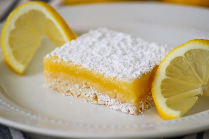 Easy Lemon Bar on a white plate with a lemon slice on each side.