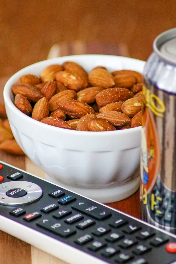 TV remote, can of beer with a bowl of Baked Spiced Almonds in background.