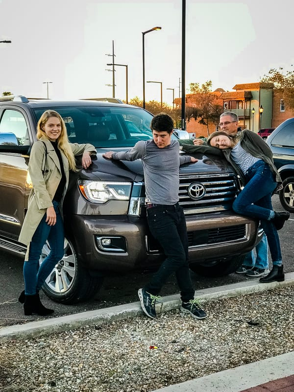 Family at the hood of the 2019 Toyota Sequoia Platinum.