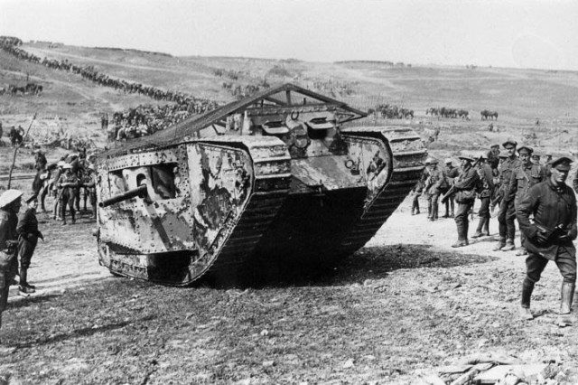 Infantrymen curiously eye the new British Army weapon – a Mark I 'tank' – before its debut in the Battle of Flers-Courcelette on 15 September 1916. Here, a 'C' Company 'Male' tank, with 6-pounder naval gun in each side sponson, prepares for action with a British unit.