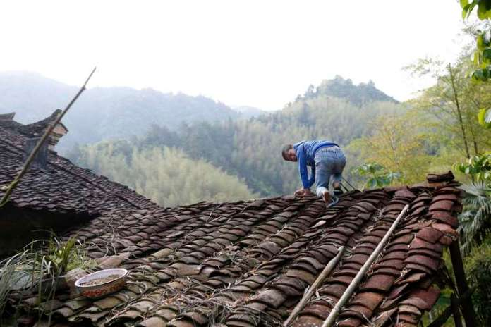 A série de imagens feitas pelo fotógrafo William Hong no início de maio, e publicada pela Reuters neste domingo, mostra cenas do menino amarrado passeando com o pai - nesta ele consegue escapar e sobe em um telhado Foto: Reuters