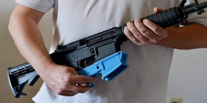 "An AR15 rifle with a bright blue 3D printed ""lower"" reciever."