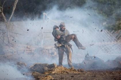Newt (Matthew McConaughey) carries Daniel (Jacob Lofland) across an active battlefield