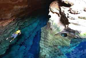 Trin swimming in the crystal clear water of a cave in Brazil