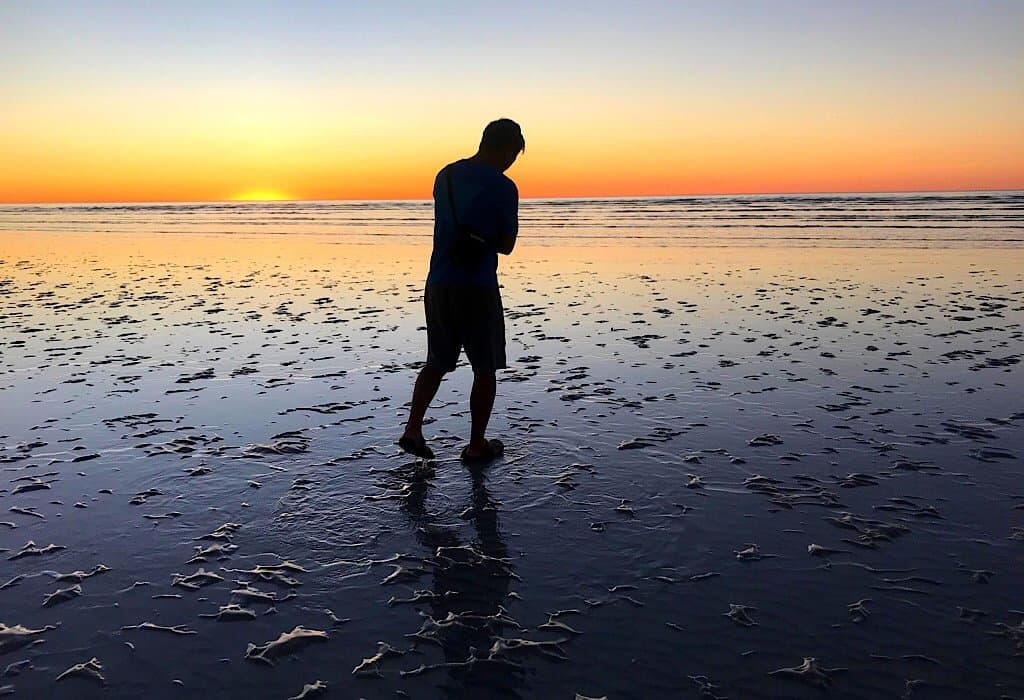 Trin standing on 80 mile beach at sunset