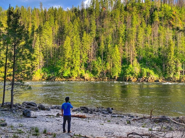 Trin standing beside the river in one of our campsites in Idaho