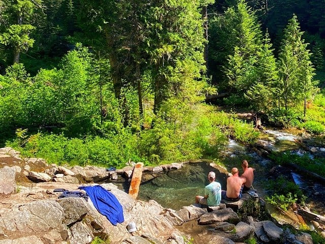 Three hikers cooling off on the edge of Wier Hot Springs