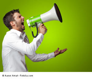 Portrait Of A Man Yelling Into A Megaphone Against Blue Background