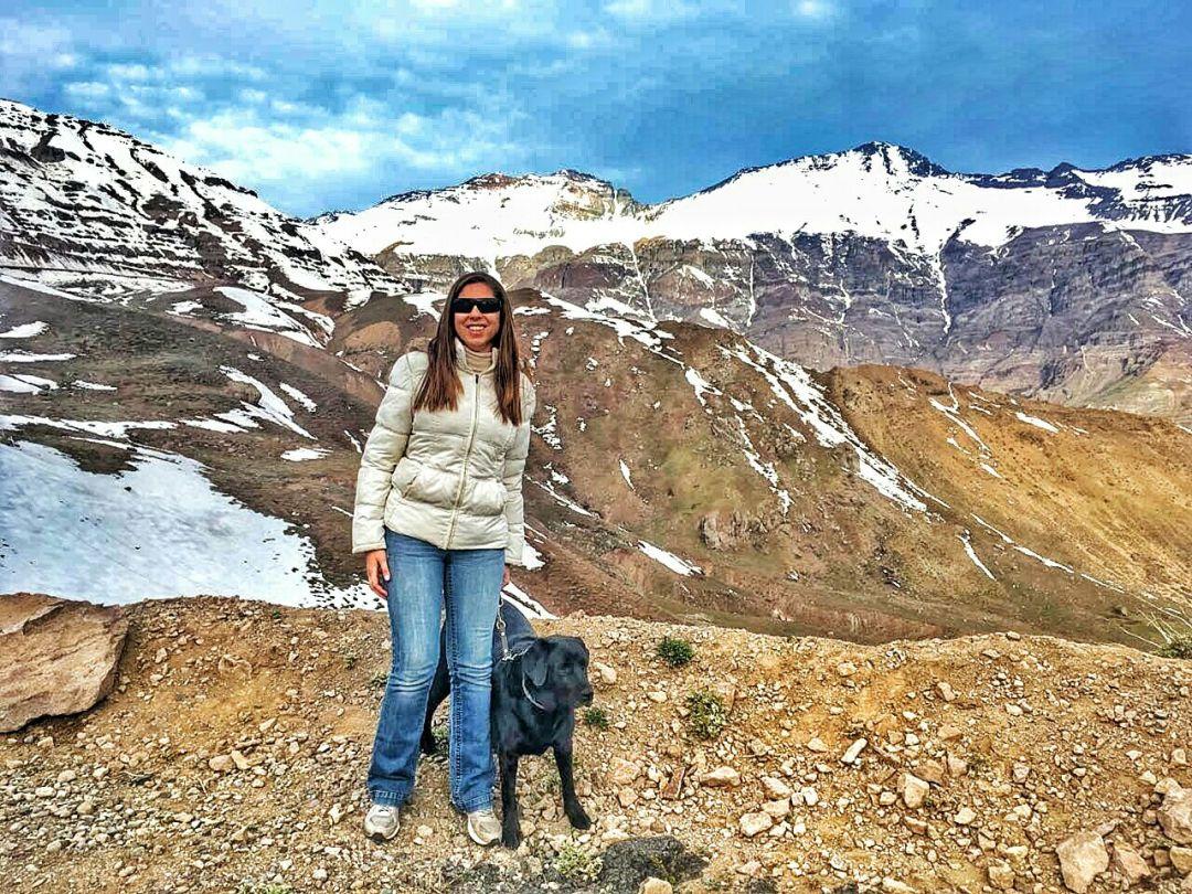 Foto principal do 4 Patas pelo Mundo, estou em pé com a Hilary sentada ao meu lado, estamos no Vale Nevado, na Cordilheira dos Andes, ao fundo montanha cheias de neve