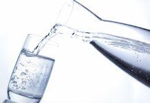 Mineralwasser in Wasserglas einschenken