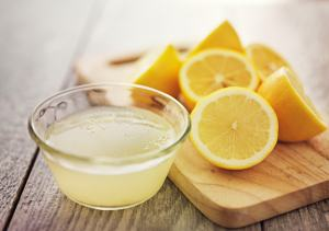 Halbe Zitronen und eine Schale mit Zitronensaft
