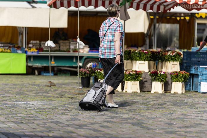 Mann zieht Einkaufstrolley