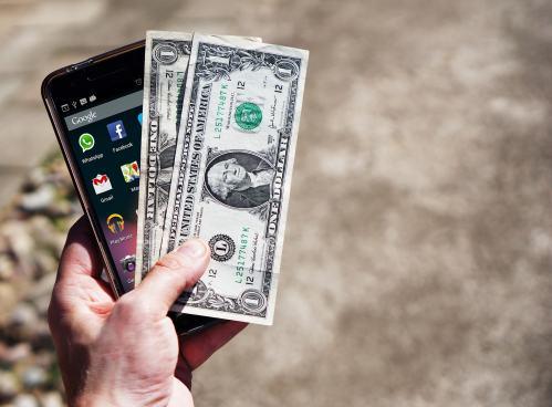 Hand mit Handy und Geld