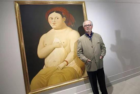 O artista fotografado diante de um dos seus quadros