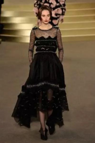 A Chanel mostrou um vestido midi bastante elaborado. Com comprimento mullet, a peça misturou transparência com bordados em prateado. A saia armada deixa o modelo ainda mais marcante - Getty Images