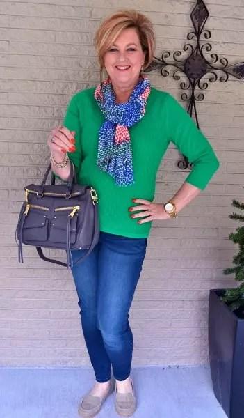 Calça comprida jeans com blusa verde e o detalhe da echarpe