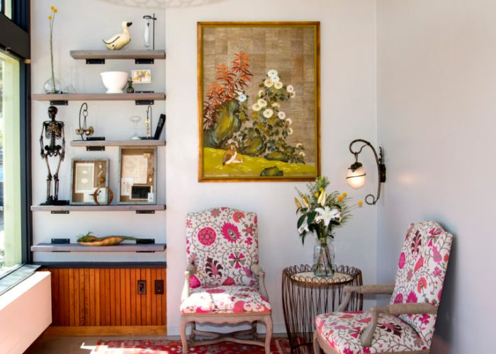 Entry way with painting of flowers and two pink floral chairs at Glow Birth & Baby Oakland