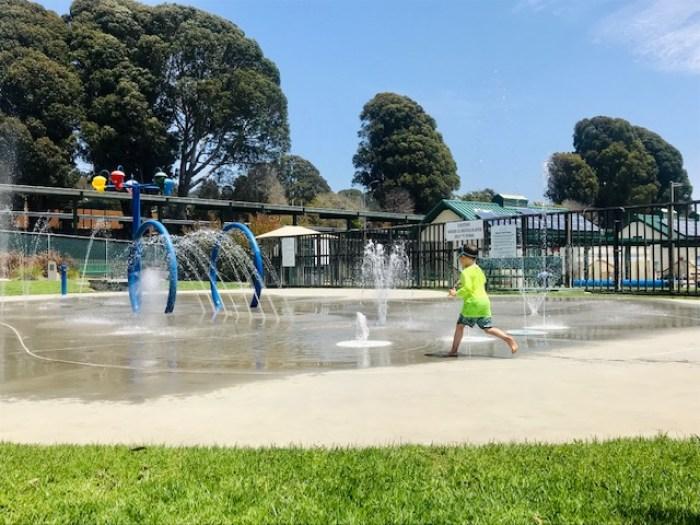 child running in splash park