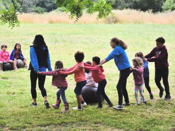 Kids dance in the field at Monkey Business camp