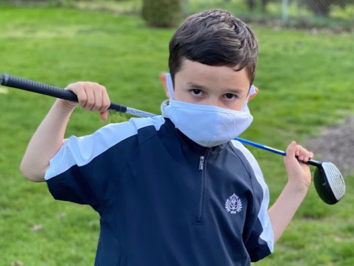 Child golfs in a mask