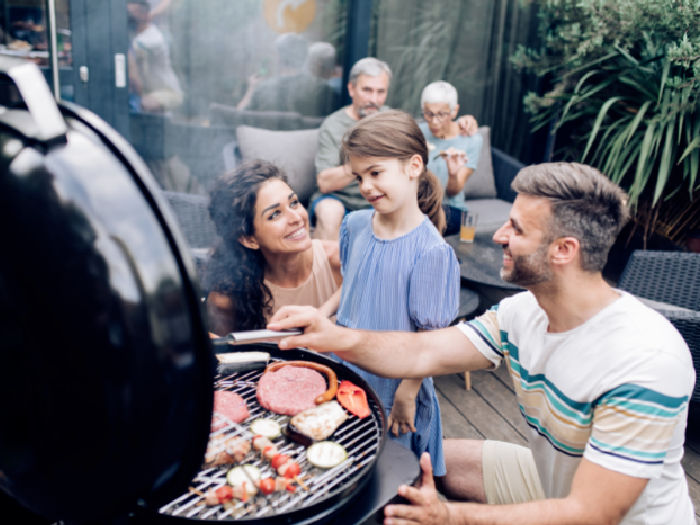 two parents and child by grill