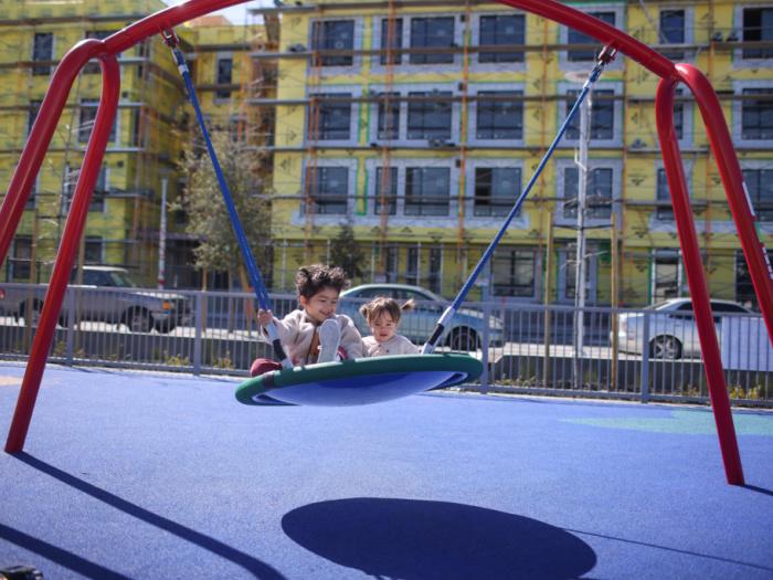 two kids on a big swing
