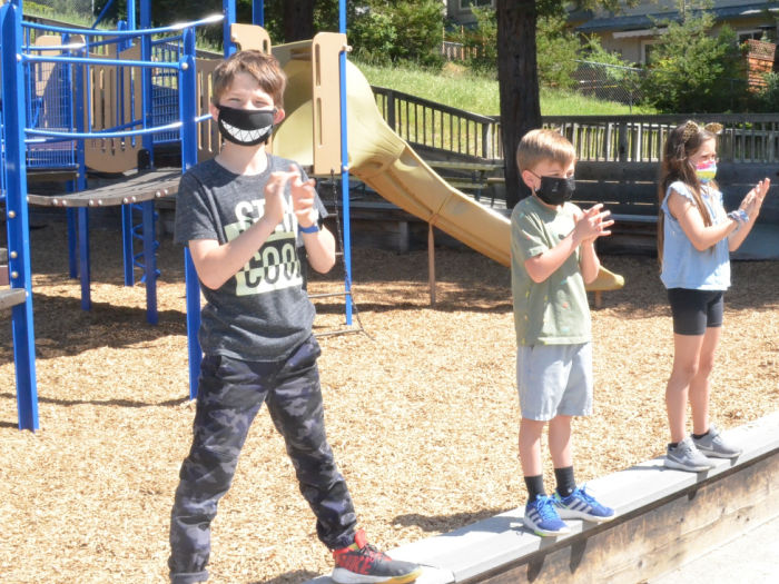 three kids at playground wearing masks