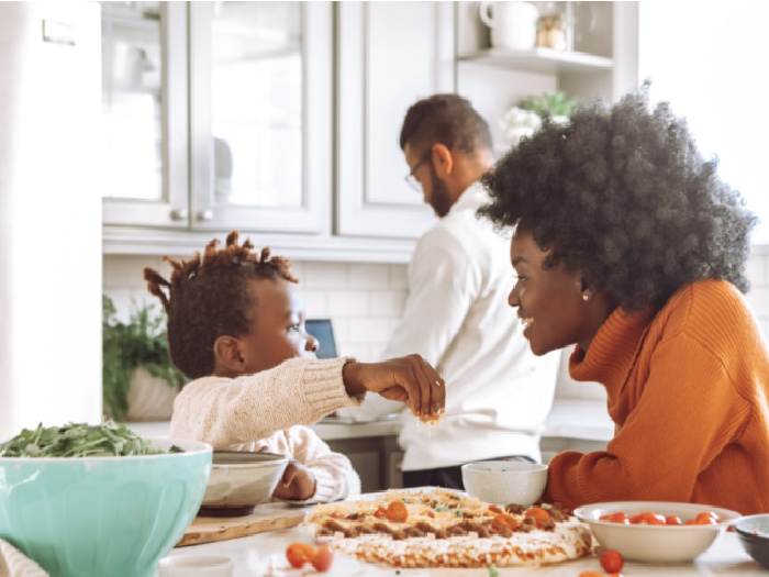 black family eating pizza in kitchen
