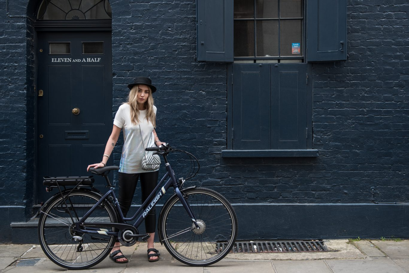 Girl with raleigh bike in front of a blue building