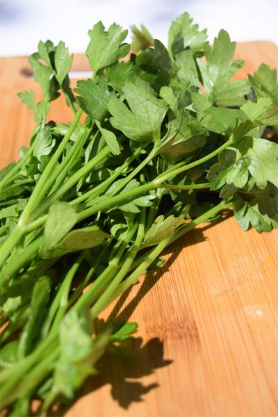 handful of flat leaf parsley on wood cutting board 5 dog farm