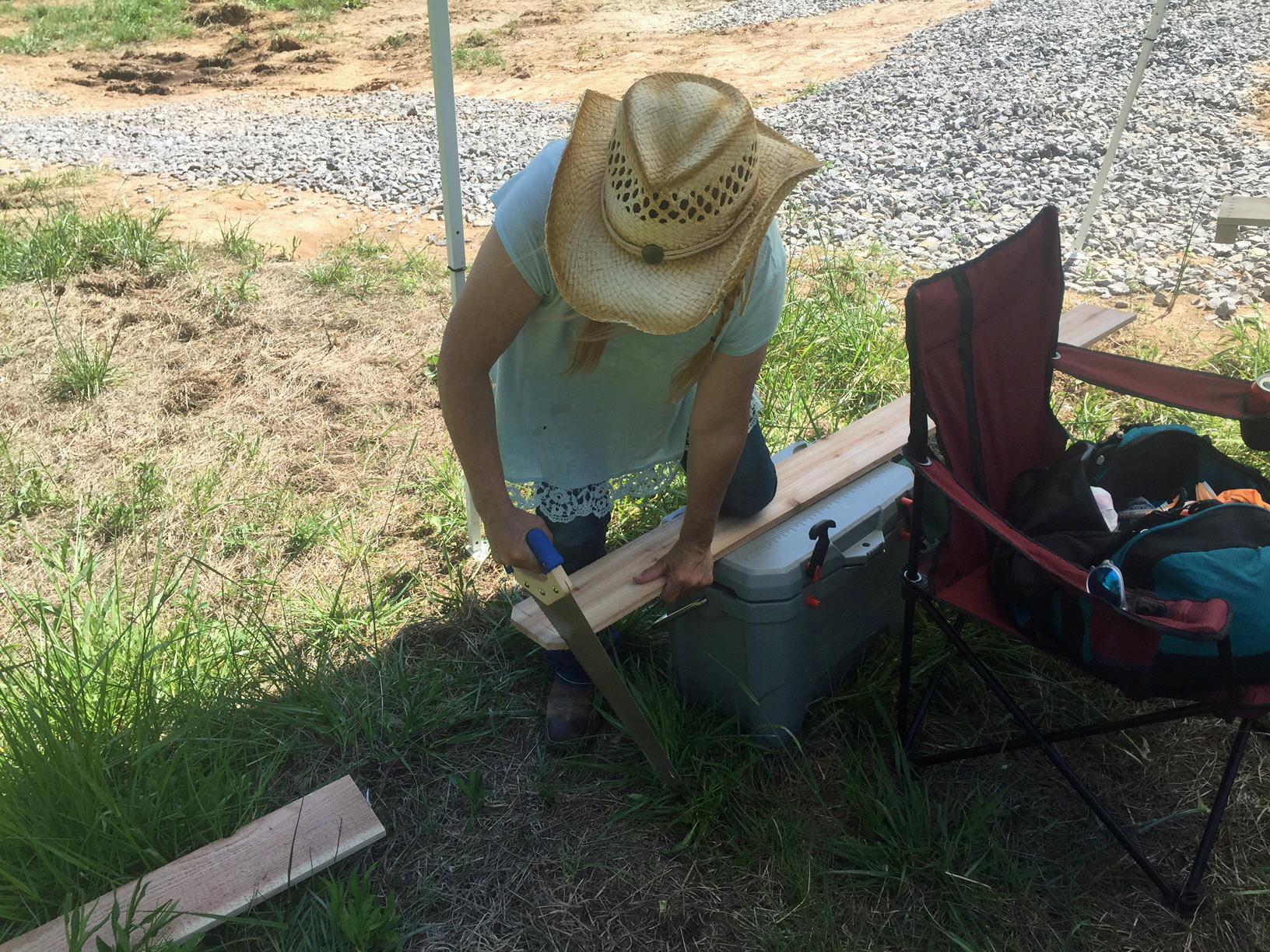 Niki Dee sawing a cedar plank 5 dog farm