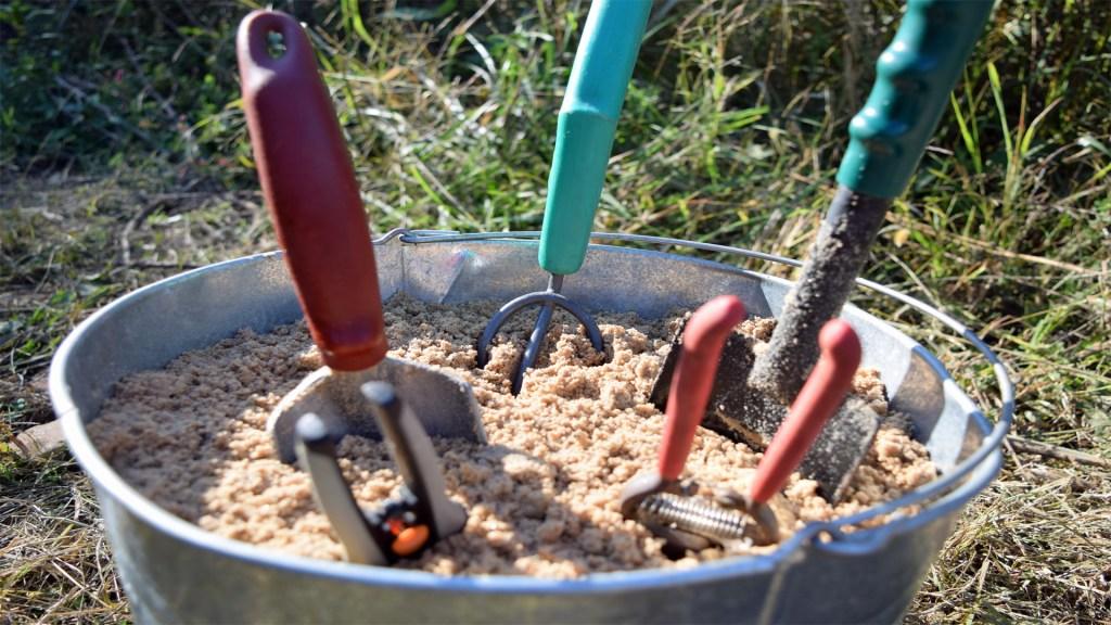 garden tools in a bucket of sand