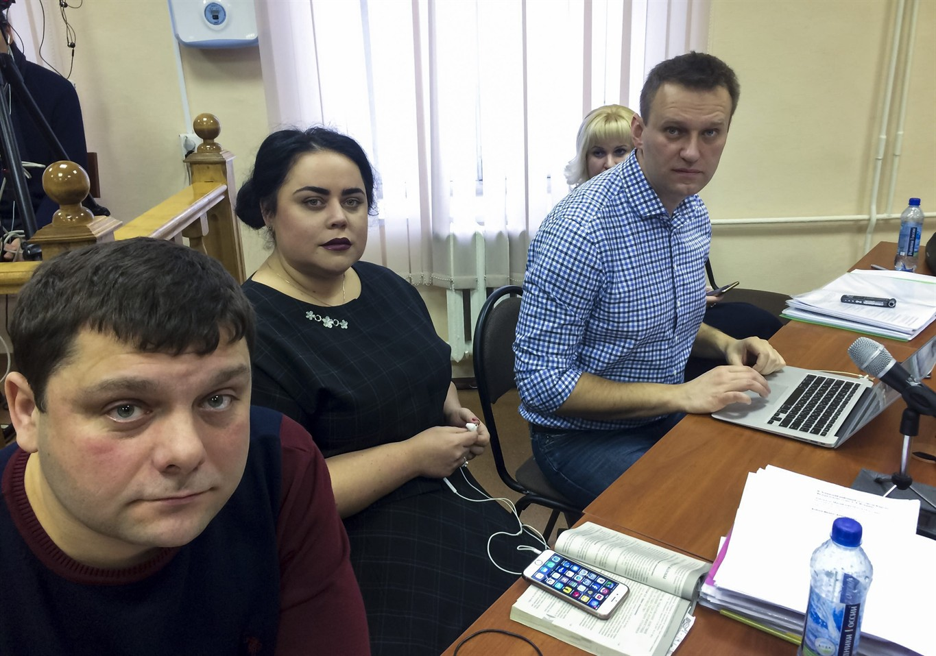 In this handout photo provided by Alexei Navalny press service Russian opposition leader Alexei Navalny, right, his former colleague Pyotr Ofitserov, left, and lawyer Svetlana Davydov, second left, sit in a courtroom in Kirov, Russia, Wednesday, Feb. 1, 2017. A retrial of Alexei Navalny for alleged embezzlement continues in the provincial city of Kirov after the original 2013 guilty verdict was overturned by the Supreme Court. (Alexei Navalny Press Service via AP)